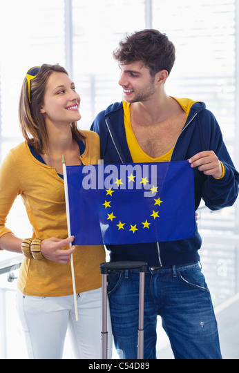Couple holding European union flag at an airport and looking at each other - Stock Image
