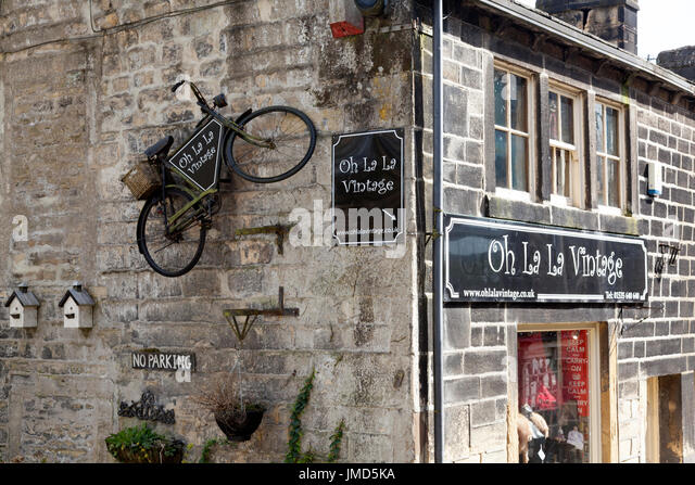Oh La La Vintage shop with old bicycle on wall, Haworth, West Yorkshire - Stock Image
