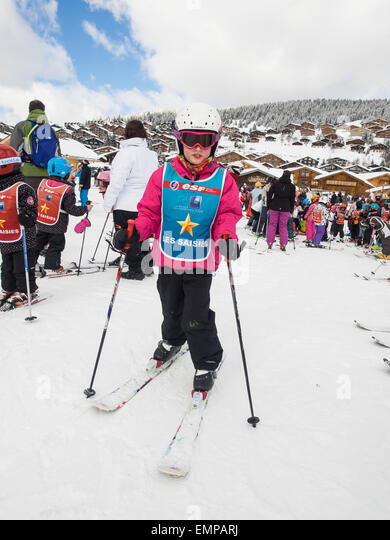 small child in skiing clothes on skis  prior to a skiing lesson with slopes  and chalets behind - Stock Image