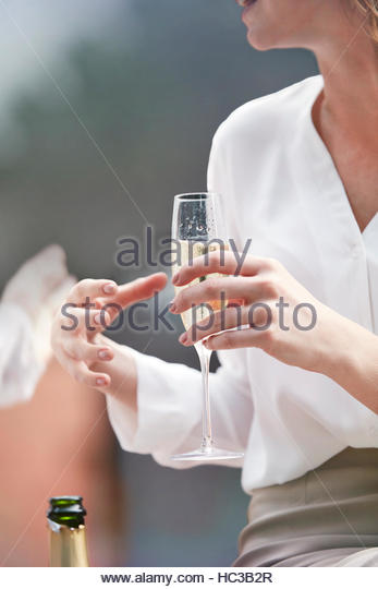 Young woman holding champagne flute. - Stock Image