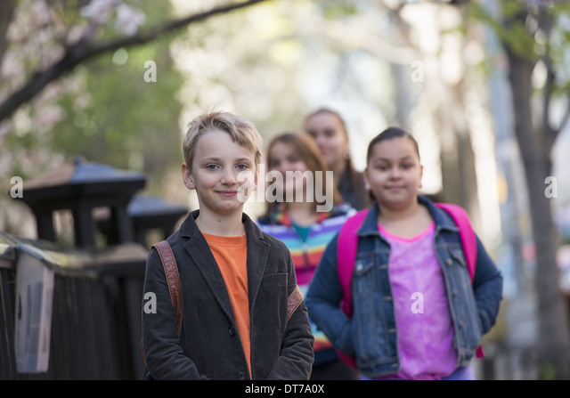 A group of children on the sidewalk, carrying bags. - Stock Image
