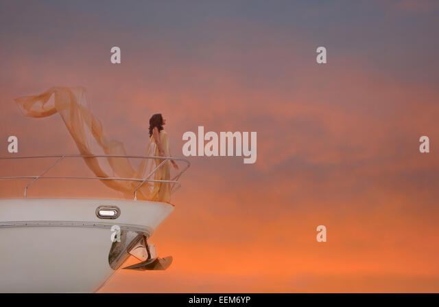 Young woman standing at railing of ship - Stock-Bilder
