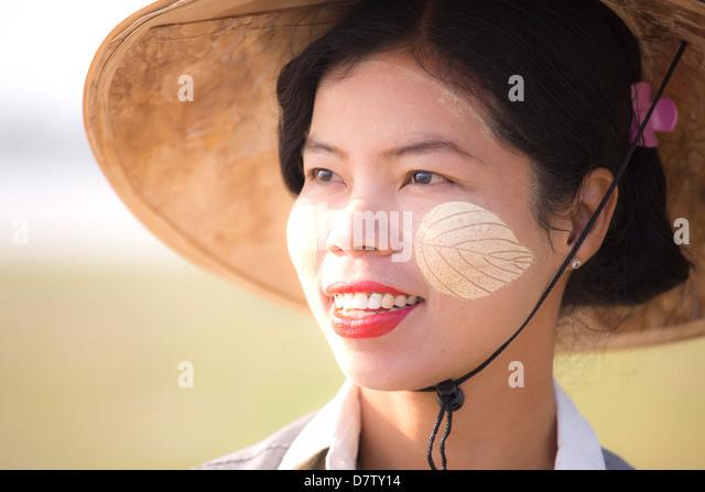 Backlit portrait of local woman wearing traditional clothing, near Mandalay, Burma - Stock Image