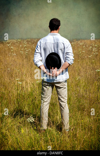 a man with a black hat standing on a field - Stock-Bilder
