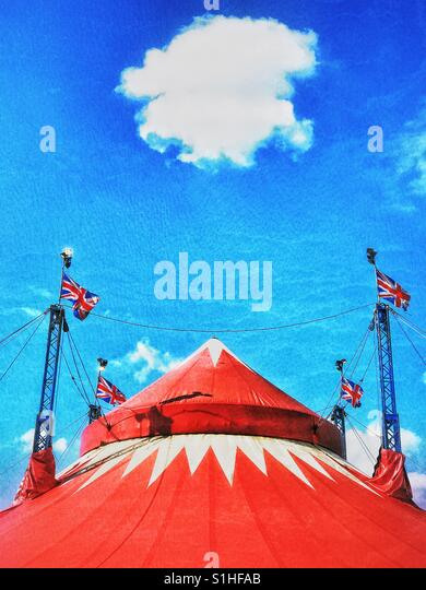 A lone cloud hangs above the top of a large circus tent in England. It's a sunny Summers day. The clowns are - Stock Image