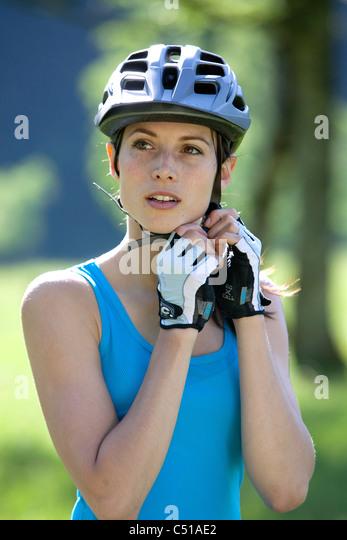 portrait of female cyclist adjusting her helmet - Stock Image