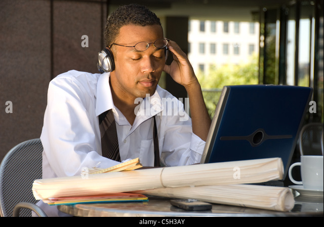 An executive engineer conducting work during his lunch hour decides to take a break and listen to some music. - Stock Image