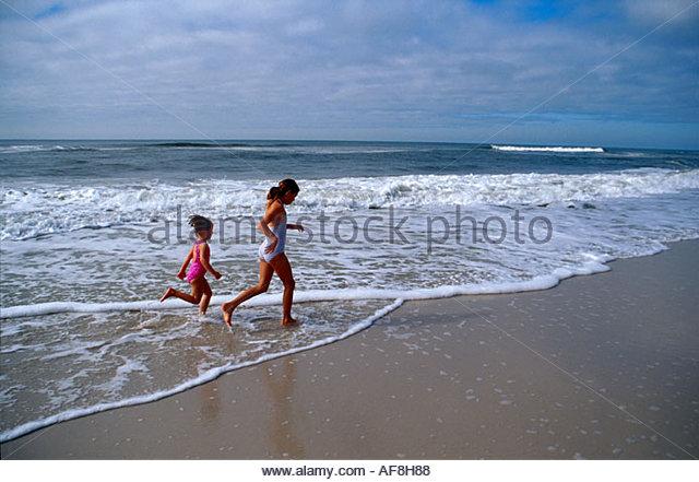 Alabama Gulf Coast Gulf Shoes West Beach girls run in surf - Stock Image