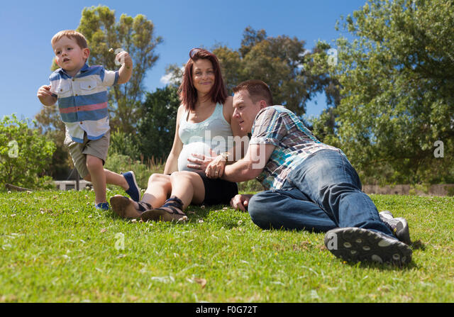 Happy parents expecting baby and enjoying sunny day with their active son in the park during sunny summer day. - Stock Image