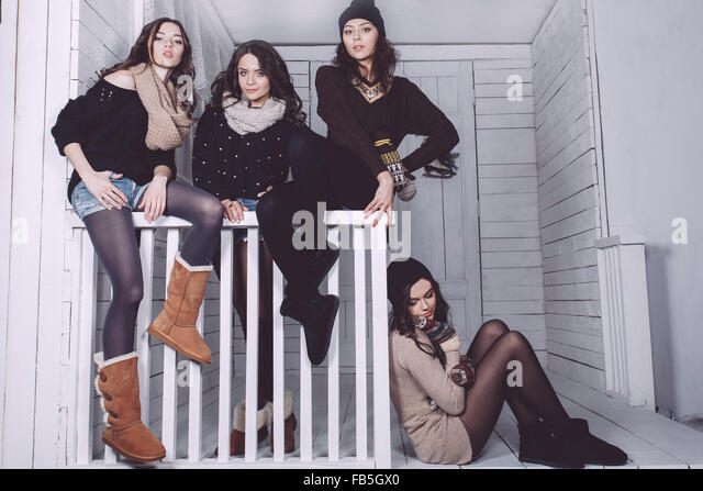 Four stylish models posing sitting on the fence - Stock-Bilder