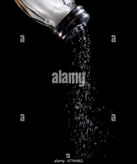 Salt shaker with salt coming out Salt shaker sodium salty falling out coming out Black background food foods - Stock Image