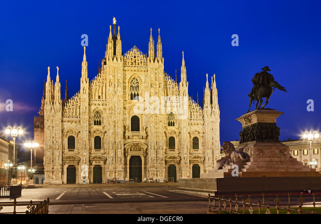 Italy Milan central city cathedral square at sunrise view on Milan duomo facade illuminated by street lamps with - Stock Image