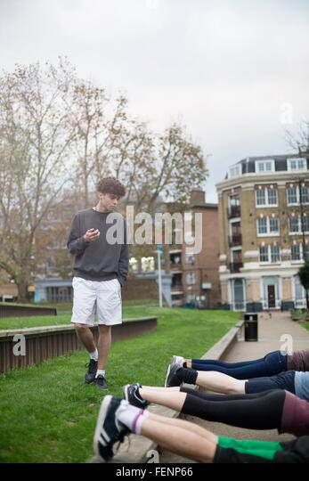 Group of adults exercising outdoors, young man holding stopwatch - Stock-Bilder