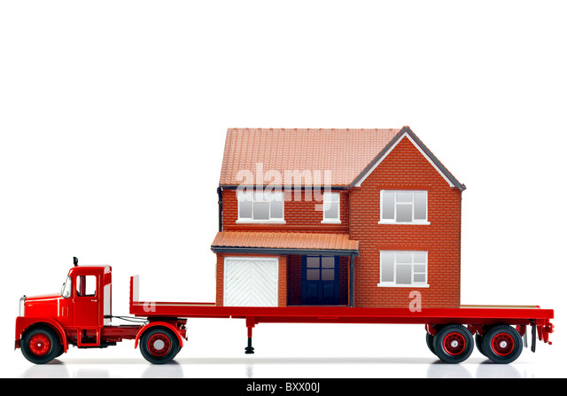 A flatbed articulated lorry loaded with a house isolated on a white background. Both are models. - Stock Image