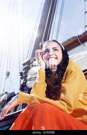 Smiling young woman on a sailing ship - Stock-Bilder