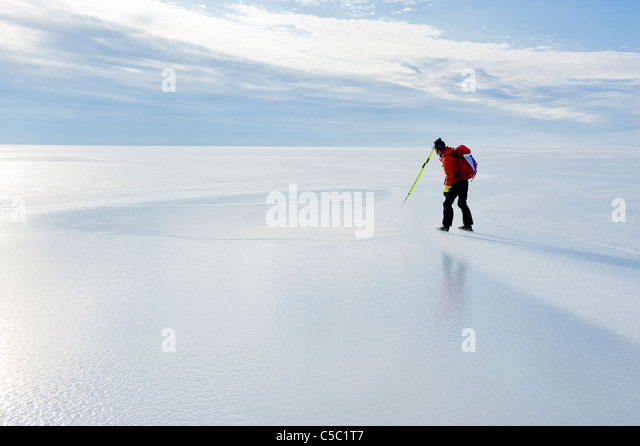 Side view of a skater on peaceful frozen lake against cloudy sky - Stock Image
