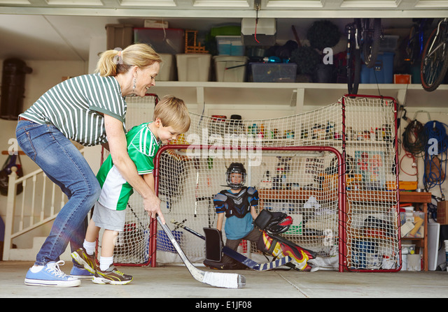 Mother playing hockey in garage with two sons - Stock Image