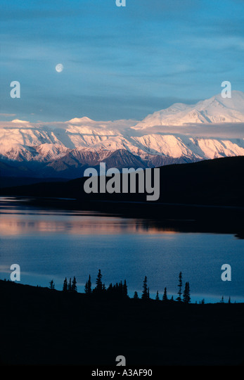 Denali National Park Alaska USA Mt McKinley and the Alaska Range reflection in Wonder Lake Sunrise and Moonset at - Stock Image