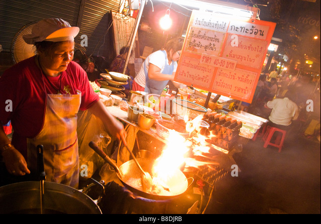Woman cooking stir fry Thai Chinese food on a night market Thanon Yaowarat road in Chinatown central Bangkok Thailand - Stock Image