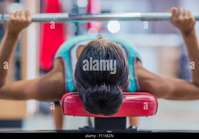 Young woman workout with barbell on the bench in fitness gym - Stock-Bilder