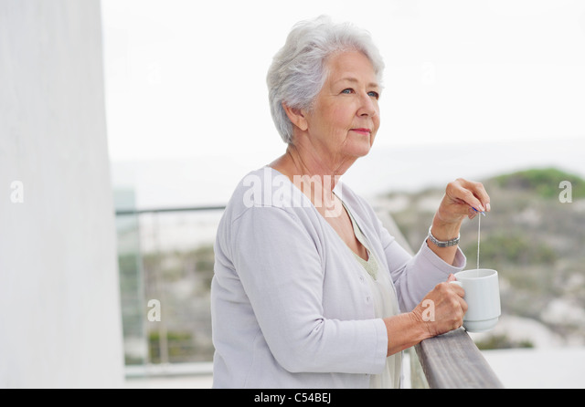 Senior woman holding a coffee cup - Stock Image