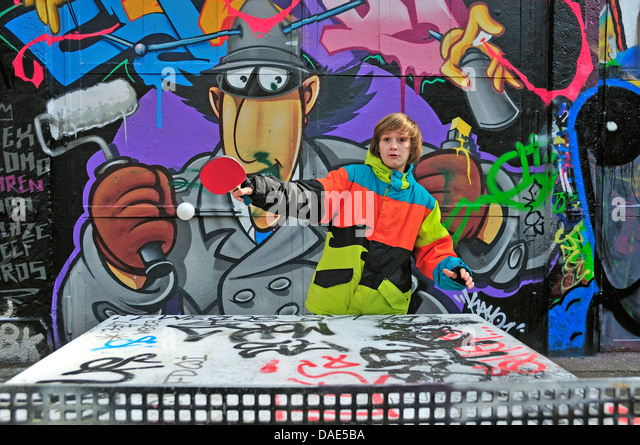 twelve-year-old boy playing table tennis in front of graffiti wall, Germany, North Rhine-Westphalia, Cologne - Stock Image