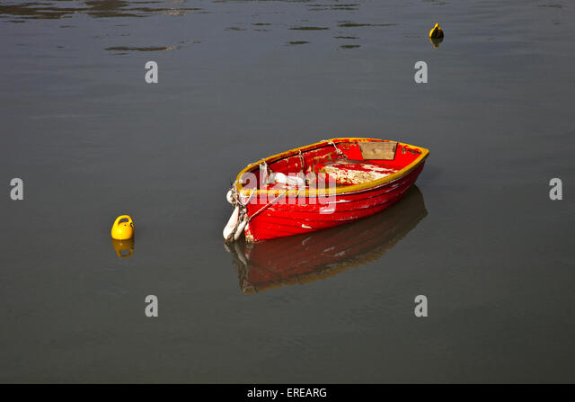 Colourful rowing boat moored in the harbour at Lyme Regis on the Jurassic Coast, Dorset, England, UK - Stock Image