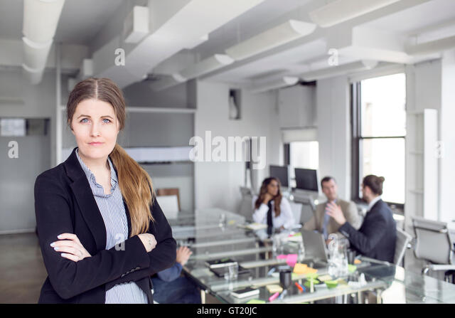 Portrait of confident businesswoman standing with colleagues discussing in background - Stock-Bilder
