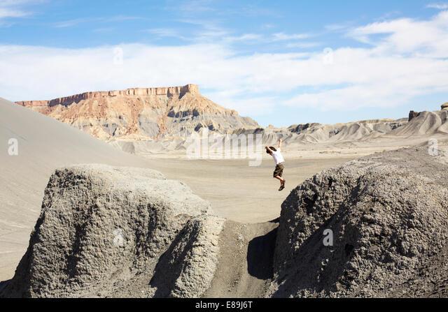 Boy jumping from rocks in the desert - Stock-Bilder