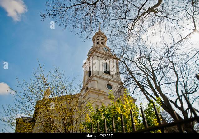 St. Alfege and trees against blue sky - Stock-Bilder
