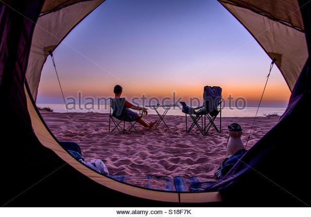 Watching the sunset on a wild beach in  the Sultanate of Oman (picture taken from the tent) - Stock-Bilder