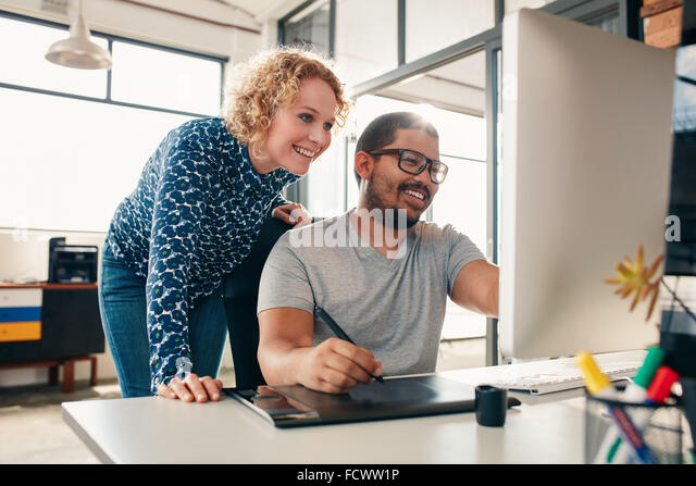 Two young male and female designers working together, with man editing artwork using graphics tablet and a stylus. - Stock Image
