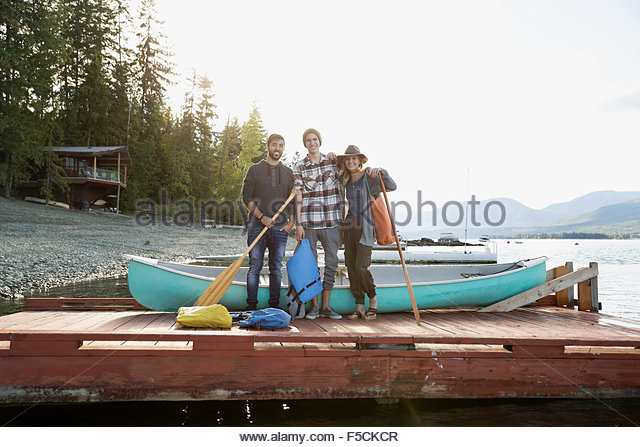 Portrait friends with canoe and paddles lake dock - Stock Image