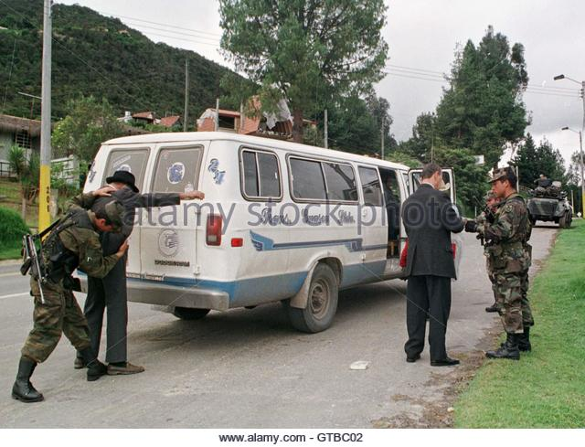 Colombian soldiers search a local bus and frisk passengers at a road block on a road on the outskirts of Bogota - Stock Image