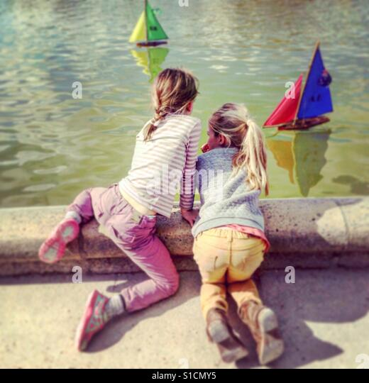 Girlfriends watch the toy boats at Luxembourg Park Paris, France. - Stock-Bilder