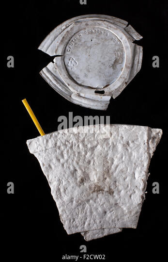 Flattened dirty styrofoam  coffee cup with yellow coffee stirrer and dirty plastic cover on black background - Stock Image