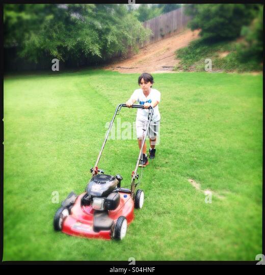 Little boy cutting grass - Stock Image