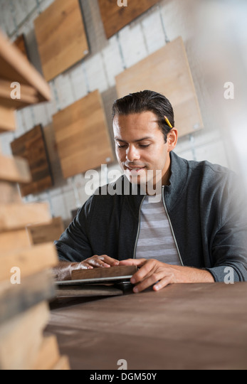 A young man in a workshop which uses recycled and reclaimed lumber to create furniture and objects. - Stock Image