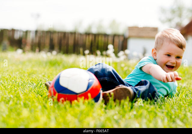 Adorable small boy playing with a soccer ball outdoors - Stock Image