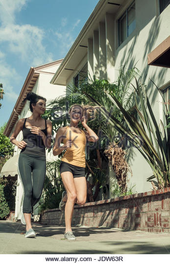 Two female friends jogging in street, low angle view - Stock-Bilder
