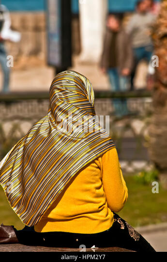 Muslim woman with bright yellow clothing sits alone by the corniche waterfront in Alexandria - Stock Image