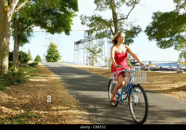 Woman riding bicycle on rural road - Stock Image