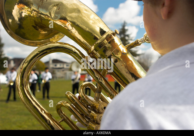 boy playing blowing gold trumpet instrument trombone at celebration school event parade sunny day clouds people - Stock Image