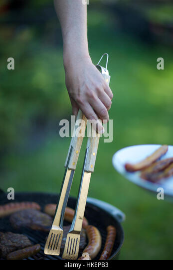human hand cooking sausages on barbecue. tongs, meat, steak, grilled meat. - Stock-Bilder