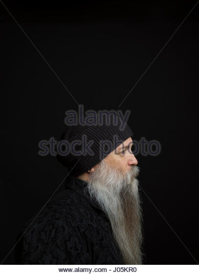 Profile portrait serious hipster man with long gray beard and stocking cap against black background - Stock Image