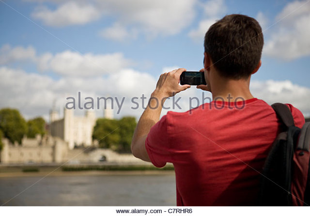A mid-adult man  taking a photograph of the Tower of London - Stock Image