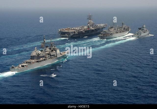 Guided-missile cruiser USS Hue City (CG 66) astern of the German navy frigate FGS Hamburd (F220), the aircraft carrier - Stock Image