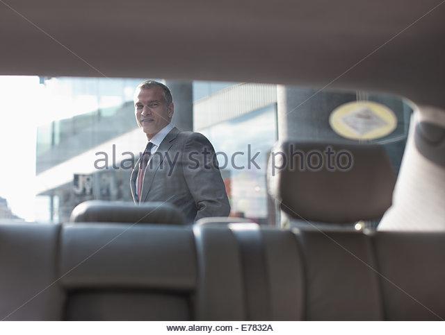 Businessman walking past car - Stock-Bilder