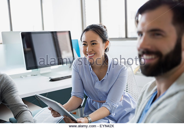 Business people with digital tablet in office - Stock Image