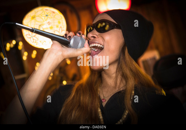 Woman wearing hat and sunglasses singing in microphone - Stock Image